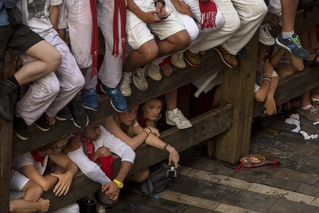 Revelers gather to watch Jandilla fighting bulls running at the San Fermin festival, in Pamplona, Spain, Tuesday, July 7, 2015. (Photo by Andres Kudacki/AP Photo)