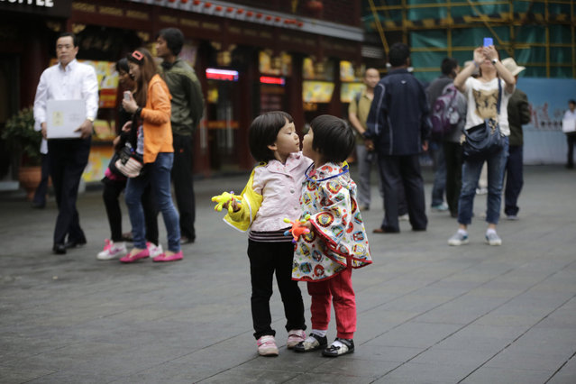 Young visitors speak to each other at Yuyuan Garden, one of the most famous tourist destinations in Shanghai, China, Thursday, May 30, 2013. (Photo by Eugene Hoshiko/AP Photo)