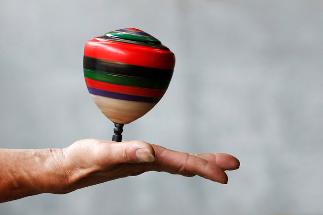 A spinning top is seen on a hand during a performance at Sanxia old street in New Taipei City, Taiwan May 8, 2016. (Photo by Tyrone Siu/Reuters)