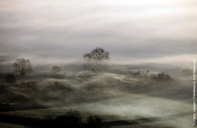 Mist and fog covers fields as the sun rises over the Somerset Levels in Glastonbury, England