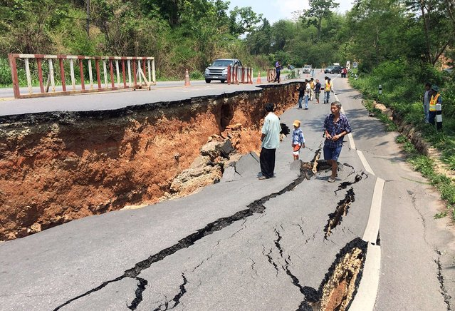People walk past cracks on a highway a day after a 6.0-magnitude quake struck in Thailand's northern province of Chiang Rai, on May 6, 2014. An elderly woman died and 23 other people were injured after a strong earthquake shook northern Thailand, an official said on May 6, as aftershocks continued to rattle the mountainous region popular with tourists. (Photo by AFP Photo/STR)