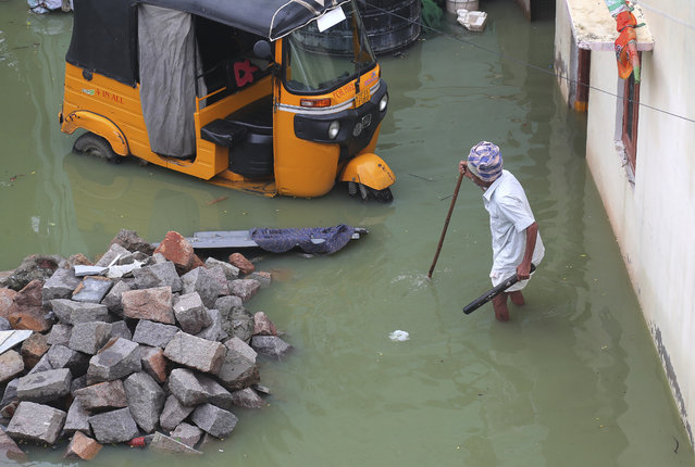 An Indian man wades through a street inundated with flood waters after heavy rainfall in Hyderabad, India, Wednesday, September 25, 2019. India receives its monsoon rains from June to September. (Photo by Mahesh Kumar A./AP Photo)