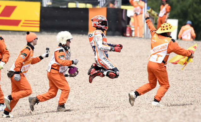 Spain's Marc Marquez celebrates with track marshals after winning the MotoGP race at the Sachsenring circuit in Hohenstein-Ernstthal, Germany, Sunday, July 12, 2015. (Photo by Jens Meyer/AP Photo)