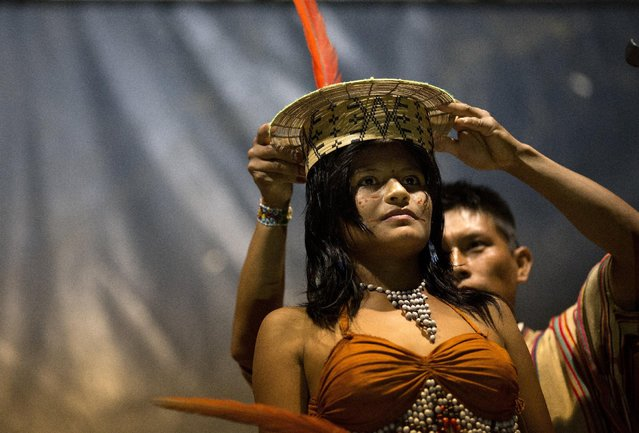 """In this June 23, 2015 photo, Beysi Anaya, 17, representing the Sampantuari village, is crowned the beauty contest winner during the annual festivities marking the founding of the Ashaninka community of Otari Nativo, Pichari, Peru. """"The little red dots are my happiness"""", said Anaya, who traveled three hours by car from her native valley community to compete in the beauty contest. (Photo by Rodrigo Abd/AP Photo)"""
