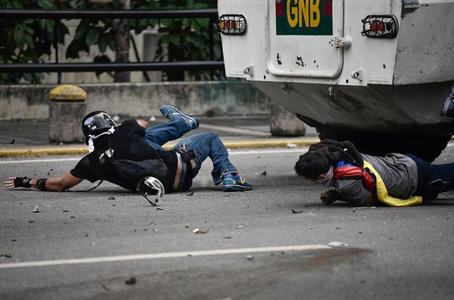Opposition activists are run over by a charging National Guard riot control vehicle during a protest against Venezuelan President Nicolas Maduro, in Caracas on May 3, 2017. (Photo by Carlos Becerra/AFP Photo)