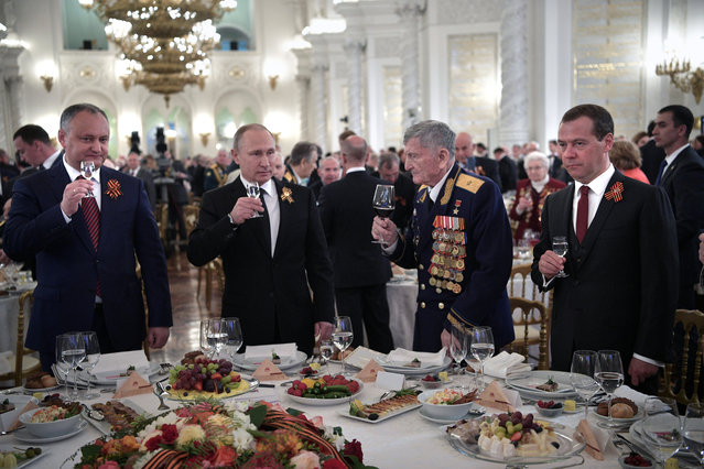 Russian President Vladimir Putin, Prime Minister Dmitry Medvedev, Moldovan President Igor Dodon, and World War II veteran, Hero of the Soviet Union Sergei Kramarenko attend the Victory Day reception after the military parade, at the Kremlin in Moscow, Russia on May 9, 2017. (Photo by Aleksey Nikolskyi/Reuters/Sputnik/Kremlin)