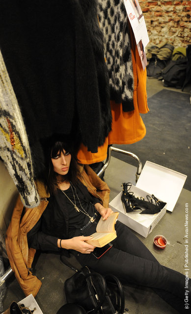 A model reads her book backstage at the Iceberg Autumn/Winter 2012/2013 fashion show as part of Milan Womenswear Fashion Week