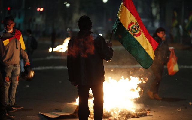 Protesters against the reelection of President Evo Morales gather around a burning barricade, in La Paz, Bolivia, Thursday, October 31, 2019. Violence has escalated since Morales was declared the winner of the Oct. 20 vote amid delays in the vote count. The opposition alleges the outcome was rigged to give Morales enough of a majority to avoid a runoff election; the president denies any irregularities. (Photo by Juan Karita/AP Photo)