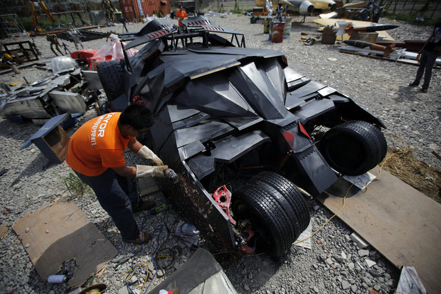 "A man works on a ""Batmobile"" replica on the outskirts of Shanghai, on May 30, 2014. Li Weilei, the owner of the replica and a local businessman, uses his spare time and money to build replicas like the ""Batmobile"", Formula One cars and ""Transformers"" for rent or sale. Li spent around 75,000 yuan ($12,000) to build the model. (Reuters/Carlos Barria)"