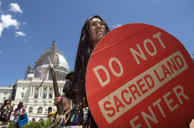An Apache activist dancer performs in a rally to save Oak Flat, land near Superior, Ariz., sacred to Western Apache tribes, in front of the U.S. Capitol in Washington, Tuesday, July 22, 2015. The land sits on top of a large copper deposit and Resolution Copper Mine enlisted the help of Sen. John McCain. McCain, R-Arz., who attached a provision into a defense bill in December 2014 that transferred 2,400 acres of federal land to them in exchange for 5,300 acres of land owned by the company. (Photo by Molly Riley/AP Photo)