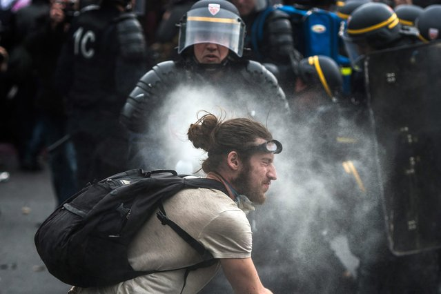 French riot police use tear gas against a demonstrator during a protest against the government's labour market reforms, at Place de la Nation, in Paris, France, 26 May 2016. (Photo by Christophe Petit Tesson/EPA)