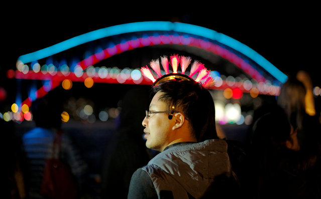 A man is seen wearing a flashing colored light headwear alongside the illuminated Sydney Harbour Bridge during the opening night of the annual Vivid Sydney light festival in Sydney, Australia May 27, 2016. (Photo by Jason Reed/Reuters)
