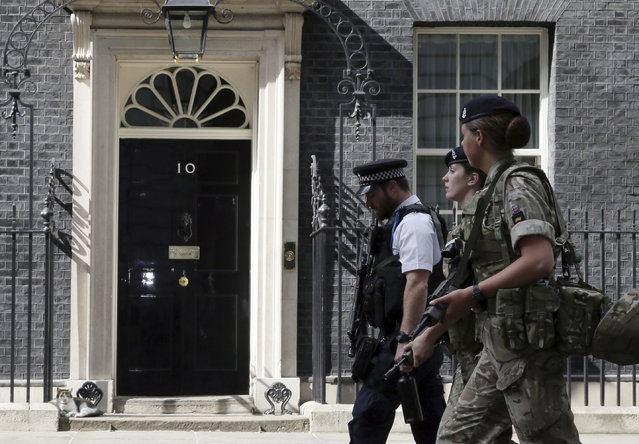 Members of the army join a police officer outside 10 Downing Street in London, Wednesday, May 24, 2017. Britons will find armed troops at vital locations Wednesday after the official threat level was raised to its highest point following a suicide bombing that killed more than 20, as new details emerged about the bomber. (Photo by Tim Ireland/AP Photo)
