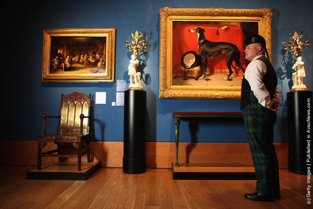 A member of staff at the Queens Gallery views a painting in the Royal Collection