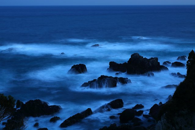 """""""I was at the southernmost cape of mainland Japan as the shades of night were falling. Due to the approaching typhoon, the waves hitting the rocks splashed high and glowed white in the twilight"""". – Takehito Miyatake. (Photo by Takehito Miyatake/Steven Kasher Gallery)"""