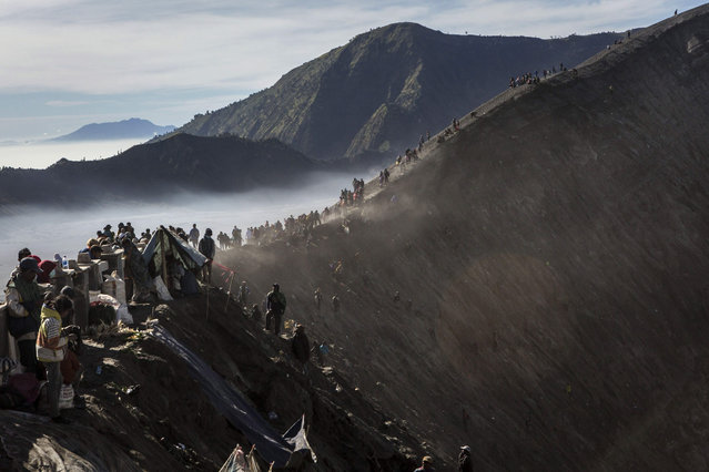 Tenggerese worshippers gather at the crater of Mount Bromo during the Yadnya Kasada Festival on August 01, 2015 in Probolinggo, East Java, Indonesia. The festival is the main festival of the Tenggerese people and lasts about a month. (Photo by Ulet Ifansasti/Getty Images)