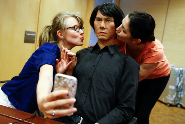Employees of Germany's biggest retailer Metro AG take a selfie as they kiss HI-4, a life-size humanoid robot, at Metro's headquarters in Duesseldorf, Germany, June 7, 2016. The android, modelled after its Japanese inventor Hiroshi Ishiguro, a professor at Osaka's University, is made of a metal skeleton, plastic skull and silicon skin; and can be used as a human substitute for interaction via a tele-operated control system. (Photo by Wolfgang Rattay/Reuters)