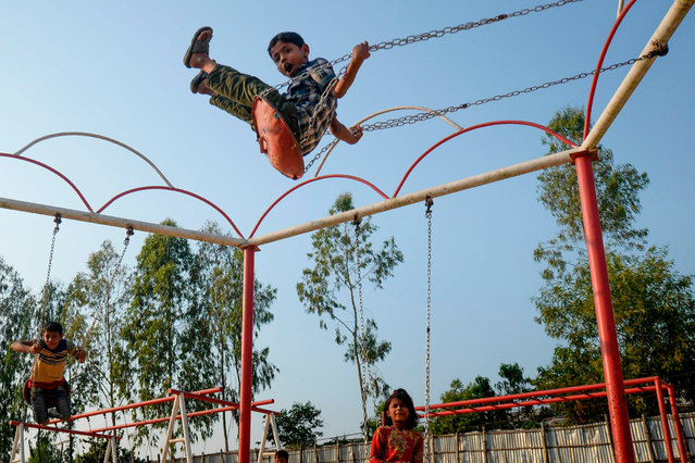 Rohingya children play on swings at a playground at Jamtola refugee camp in Ukhia on December 9, 2019. (Photo by Munir Uz Zaman/AFP Photo)