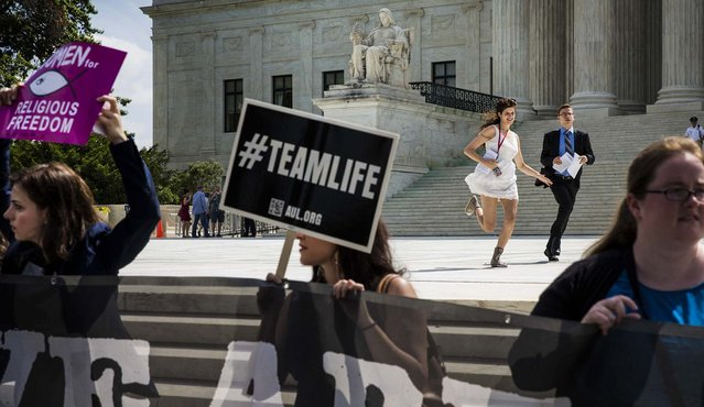 Reporters run past anti-abortion demonstrators outside of the Supreme Court with a copy of the decision striking down abortion clinic buffer zones, in Washington, on June 25, 2014. The Supreme Court on Thursday unanimously struck down a Massachusetts law that barred protests near abortion clinics. (Photo by Stephen Crowley/The New York Times)