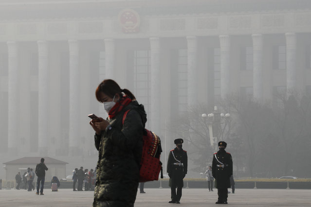 A woman walks past Chinese paramilitary policemen wearing protection masks on Tiananmen Square in Beijing as the capital of China is blanketed by heavy smog on Wednesday, January 4, 2017. China has long faced some of the worst air pollution in the world, blamed on its reliance of coal for energy and factory production, as well as a surplus of older, less efficient cars on its roads. Inadequate controls on industry and lax enforcement of standards have worsened the pollution problem. (Photo by Andy Wong/AP Photo)