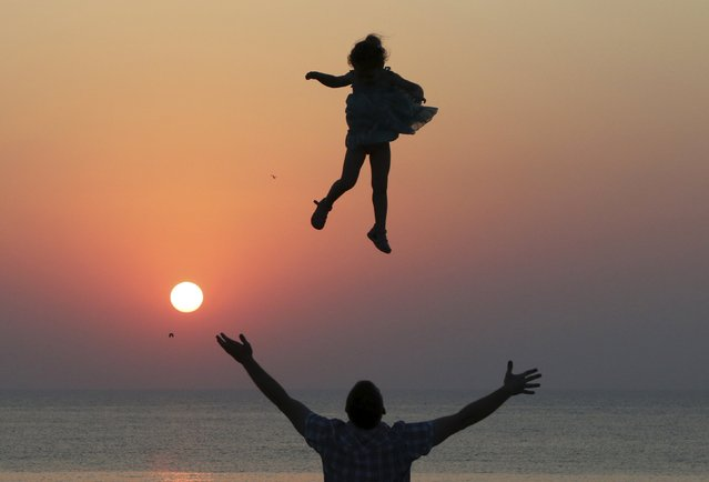A man throws a girl into the air during sunset as they spend time on the territory of Chersonesus Tavrichesky (Tauric Chersonesos) National Reserve in the Black Sea port of Sevastopol, Crimea, July 25, 2015. (Photo by Pavel Rebrov/Reuters)