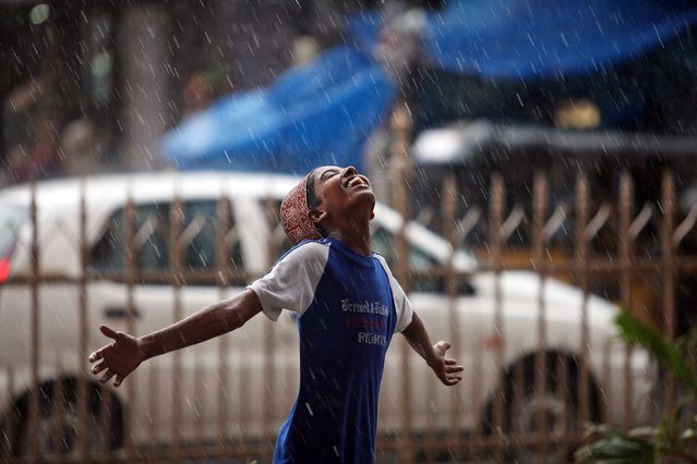 An Indian Muslim boy stretches his arms and looks skyward as rain falls in Hyderabad, India, Tuesday, July 1, 2014. (Photo by Mahesh Kumar A./AP Photo)