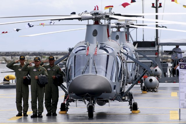 Members of the Philippine Navy salutes beside one of the two newly-acquired AW109E multi-purpose helicopter during a ceremony at the Philippine Navy headquarters in Manila August 10, 2015. (Photo by Romeo Ranoco/Reuters)