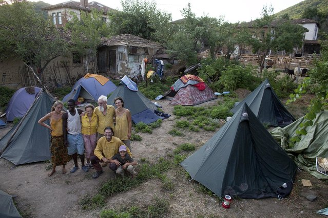 Members of the group of 22 people, newly settled in the village of Odrintsi, Bulgaria, pose for a picture, August 10, 2015. A self-described shaman who discovered the healing powers of herbs while seeing visions on his sickbed; a former consultant for IBM who ditched PowerPoint presentations to drive across Africa and an artist from Luxembourg who is a qualified plumber. (Photo by Stoyan Nenov/Reuters)