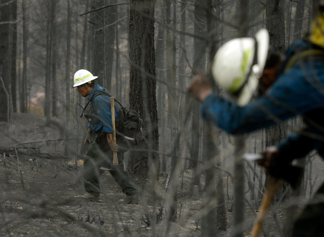 Members of Bighorn 209, a hand crew from the Crow Agency in Montana check for hot spots on the Waldo Canyon Fire west of Colorado Springs, on June 29, 2012. (AP Photo/Chris Carlson)