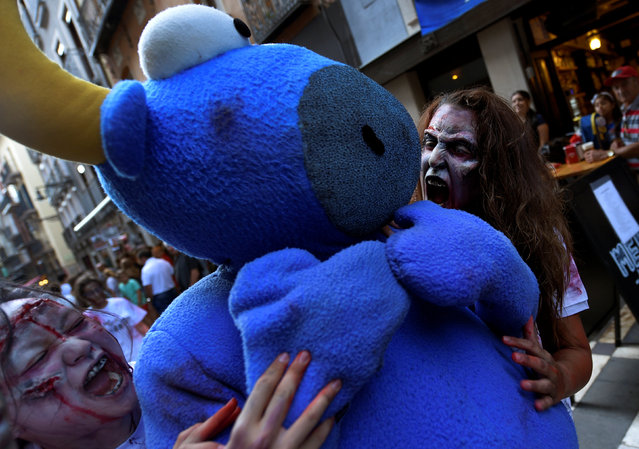 Revellers dressed as zombies bite a bull figure during an enactment of the running of the bulls a day before the start of the San Fermin festival in Pamplona, northern Spain, July 5, 2016. (Photo by Eloy Alonso/Reuters)
