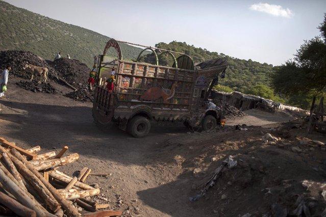 A truck drives past a coal field in Choa Saidan Shah, Punjab province, May 5, 2014. (Photo by Sara Farid/Reuters)