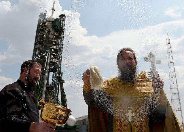 A Russian Orthodox priest blesses members of the media in front of the Soyuz MS-01 spacecraft at the launch pad of the Russian-leased Baikonur cosmodrome in Kazakhstan on July 6, 2016. NASA astronaut Kate Rubins, cosmonaut Anatoly Ivanishin of the Russian space agency Roscosmos, and astronaut Takuya Onishi of the Japan Aerospace Exploration Agency will launch at 9:36 p.m. (7:36 a.m. Baikonur time, July 7, 2016) from the Baikonur Cosmodrome in Kazakhstan. All three will spend approximately four months on the orbital complex, returning to Earth in October. (Photo by Vasily Maximov/AFP Photo)