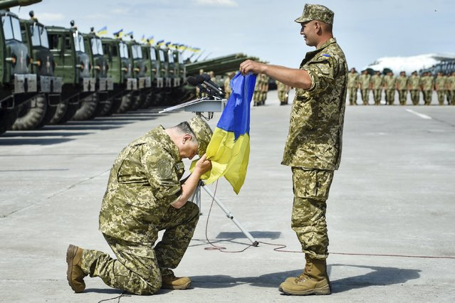 Ukraine's President Petro Poroshenko (L) attends a ceremony to hand over new weapons and military vehicles to servicemen of the Ukrainian armed forces at an air base in Chuhuiv, Kharkiv region, Ukraine, August 22, 2015. (Photo by Mykola Lazarenko/Reuters/Ukrainian Presidential Press Service)