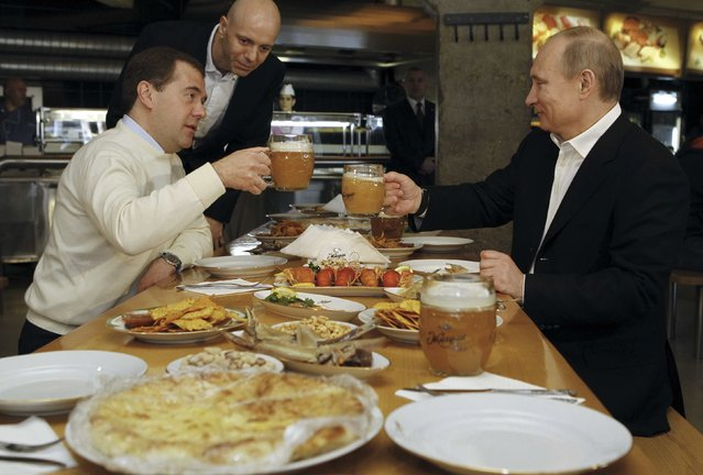 File photo of Russian President Dmitry Medvedev (L) and Prime Minister and President-elect Vladimir Putin toasting with beer during a visit to a self-service restaurant in Moscow May 1, 2012. Russia will ban fruit, vegetables, meat, fish, milk and dairy imports from the United States, the European Union, Australia, Canada and Norway, Prime Minister Dmitry Medvedev told a government meeting August 7, 2014. (Photo by Dmitry Astakhov/Reuters/RIA Novosti/Kremlin)