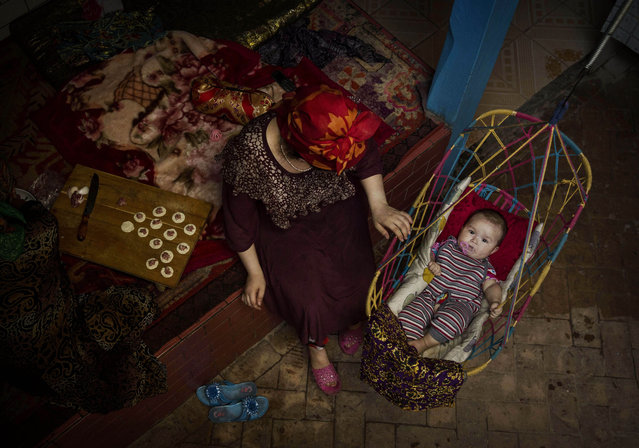 A Uyghur woman takes care of her child at home before the Eid holiday  on July 28, 2014 in old Kashgar, Xinjiang Province, China. (Photo by Kevin Frayer/Getty Images)