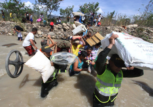 Colombian police help carry people's household belongings across the Tachira River from Venezuela, top, to Colombia, on the border that separates San Antonio del Tachira, Venezuela from Villa del Rosario, Colombia, Tuesday, August 25, 2015, during a mass exodus of Colombians. (Photo by Eliecer Mantilla/AP Photo)