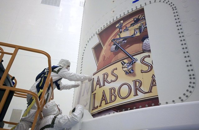 The Mars Science Laboratory (MSL) mission logo begins to take shape as technicians install it on the exterior of an Atlas V rocket's payload fairing inside the Payload Hazardous Processing Facility in Florida, on October 29, 2011. (Photo by Jim Grossmann/NASA)
