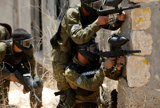 Paint from a pellet is seen in mid-air as Israeli soldiers from the Nahal Infantry Brigade use paintball guns during an urban warfare training in the West Bank Jewish settlement of Alei Zahav, near Ariel July 13, 2016. (Photo by Baz Ratner/Reuters)