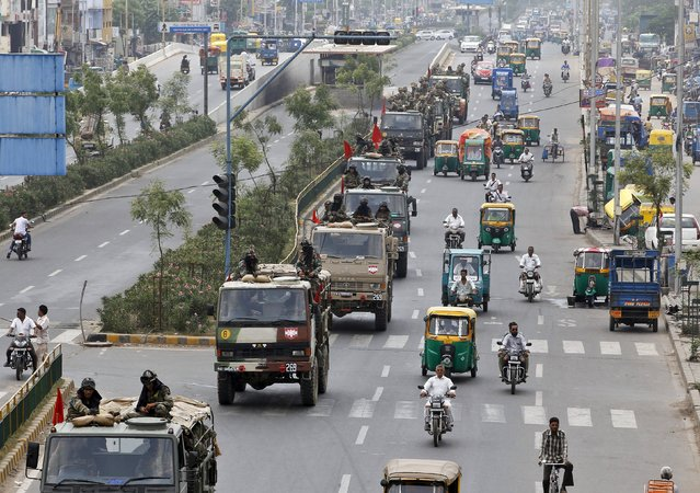 A convoy of Indian army soldiers patrols a road in Ahmedabad, India, August 27, 2015. The Indian army patrolled riot-hit areas of Prime Minister Narendra Modi's home state of Gujarat on Thursday after the death toll rose to seven in two days of caste-related violence. (Photo by Amit Dave/Reuters)