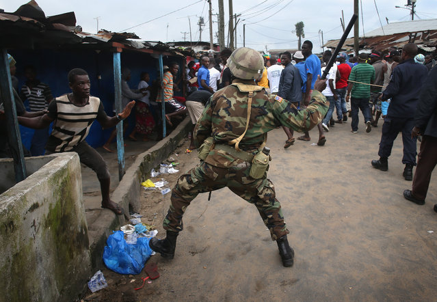 A Liberian Army soldier, part of the Ebola Task Force, beats a local resident while enforcing a quarantine on the West Point slum on August 20, 2014 in Monrovia, Liberia. The government ordered the quarantine of West Point, a congested seaside slum of 75,000, on Wednesday, in an effort to stop the spread of the virus in the capital city. (Photo by John Moore/Getty Images)