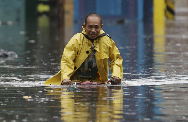 """A man pedals his bicycle along a flooded street in Manila, Philippines on Tuesday, September 12, 2017. Classes in schools and work in government offices have been suspended in the capital and nearby provinces as heavy rains pour causing floods in low-lying areas due to Tropical Depresion """"Maring"""". (Photo by Aaron Favila/AP Photo)"""