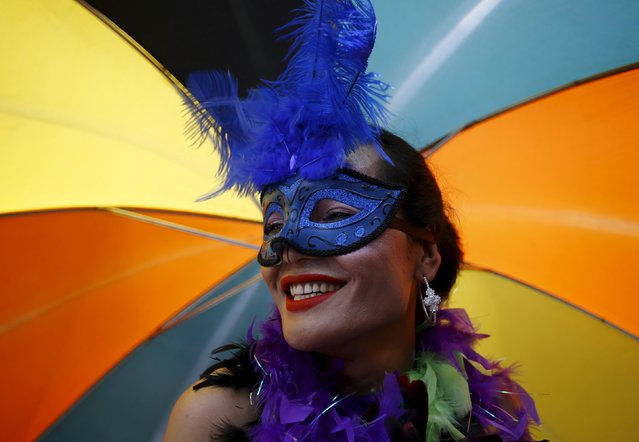 A reveller carrying an umbrella takes part in a LGBT (lesbian, gay, bisexual, and transgender) pride parade to mark Gaijatra Festival, also known as the festival of cows, in Kathmandu, Nepal August 30, 2015. (Photo by Navesh Chitrakar/Reuters)