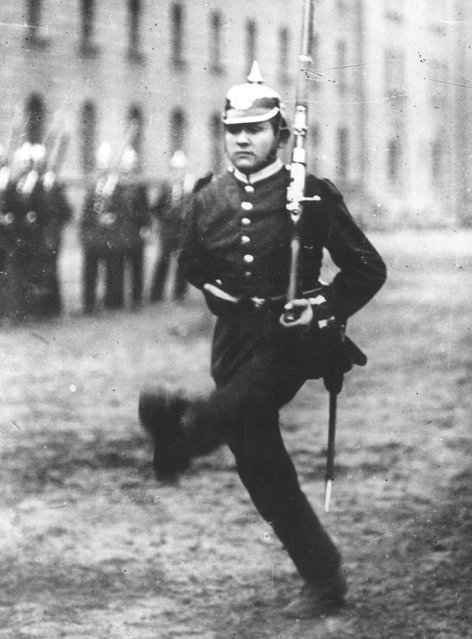 """A German infantryman marching the """"goose step"""" at a military parade, 1914."""