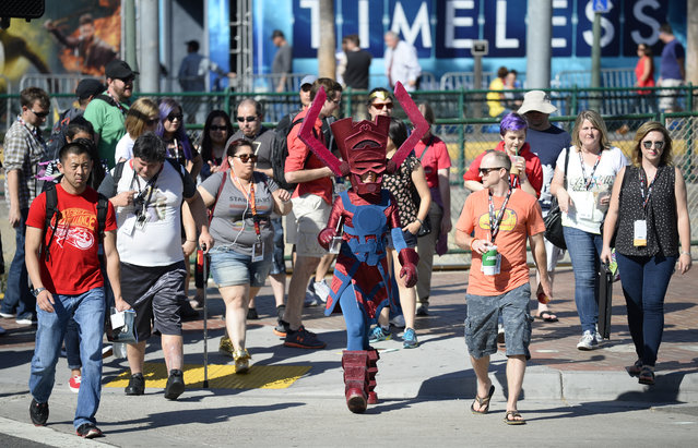 Bunny Knowble, dressed Galactus Eater of Worlds, crosses the street with the crowd on the way to Preview Night at Comic-Con International held at the San Diego Convention Center Wednesday July 20, 2016, in San Diego. (Photo by Denis Poroy/Invision/AP Photo)