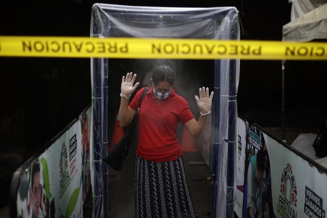 A woman goes through a disinfection area with sprinklers before entering the municipal market of Santa Tecla, El Salvador, 14 April 2020. El Salvador is living its first day of home quarantine without the support of a state of emergency, which came to end at midnight, to avoid the spread of the SARS-CoV-2 coronavirus which causes the COVID-19 disease. (Photo by Rodrigo Sura/EPA/EFE)