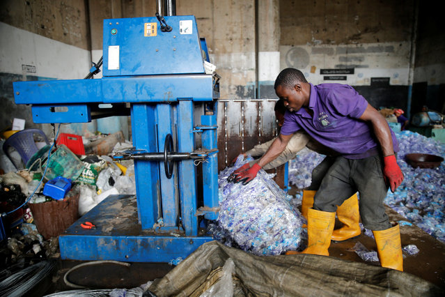 Men remove a block of compressed waste from a machine at the Wecycler waste recycling centre in Ebutte Meta district in Lagos, Nigeria July 28, 2016. (Photo by Akintunde Akinleye/Reuters)