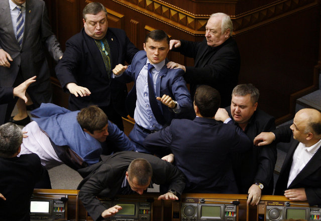 """Members of Parliament of the Svoboda party fight with Members of Parliament of the Communist party in the Ukrainian parliament on April 8, 2014, during the debates focused on a law toughening responsibility for separatism. Ukraine's acting president said today he would treat Russian separatists who have seized buildings in the east of the country as """"terrorists"""" who will be prosecuted with the full force of the law. (Photo by Yuriy Kirnichny/AFP Photo)"""