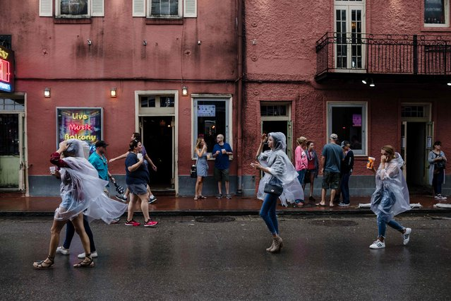Visitors walk in the French Quarter in New Orleans on October 7, 2017. US Gulf Coast residents scrambled with last-minute preparations Saturday as the outer bands of Hurricane Nate began lashing New Orleans amid fears it could intensify into a more powerful Category Two storm. Nate spawned widespread flooding and left dozens of people dead in Central America, the latest in a series of deadly storms to hammer Caribbean islands, Mexico and the southeastern US in this exceptionally busy hurricane season. (Photo by Bryan Tarnowski/AFP Photo)