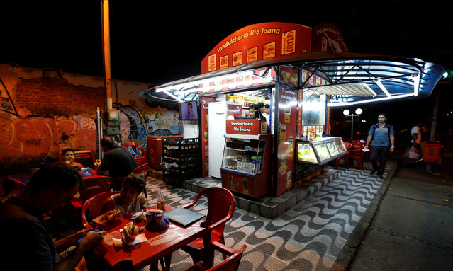 """A view of a kiosk selling podrao, the Portuguese word for """"rotten"""" (a hotdog or burger type sandwich assembled according to taste), is seen in Rio de Janeiro, Brazil, April 8, 2016. (Photo by Sergio Moraes/Reuters)"""