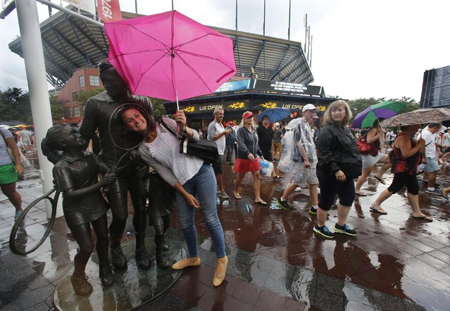 A tennis fan stops for a photo as she exits the Billie Jean King National Tennis Center during a rain delay at the 2014 U.S. Open tennis tournament, Sunday, August 31, 2014, in New York. (Photo by Elise Amendola/AP Photo)